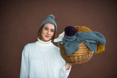 woman holding basket with hats and scarfs