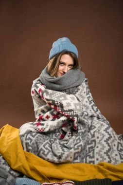 Woman sitting wrapped in blankets