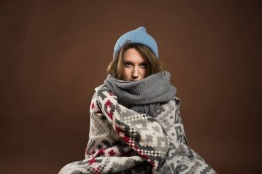 serious girl wrapped in warm blankets