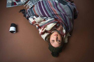 girl lying on floor wrapped in blankets