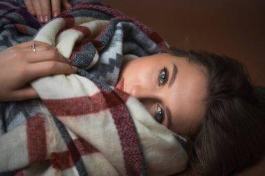 Woman lying on floor wrapped in blanket