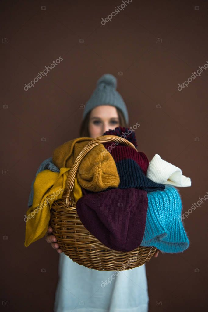 woman showing basket with hats and scarfs