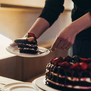 woman putting piece of cake on plate