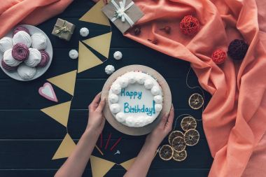 woman putting birthday cake on table