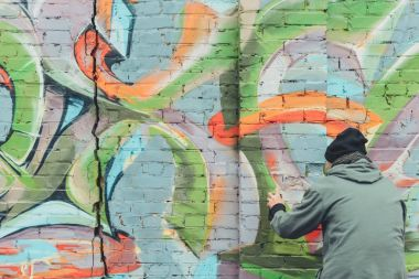 back view of man painting colorful graffiti on wall
