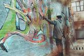 Pouliční malíř malovat barevné graffiti na zeď