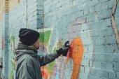 pouliční umělec Malování barevné graffiti na zdi