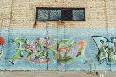 plechovky s sprejem a žebřík poblíž barevné graffiti na zdi budovy ve městě
