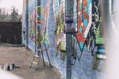 a spray-festék és színes graffitik a falon a város épület közelében létra kannák