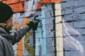 man painting colorful graffiti on wall