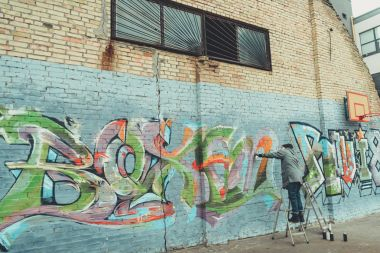 low section view of man painting colorful graffiti on building