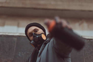 selective focus of street artist in respirator holding can with spray paint