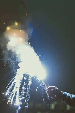 cropped view of male hand with smoke bomb with sparks at night