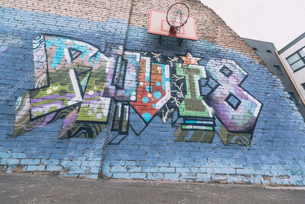 colorful graffiti on wall with basketball hoop