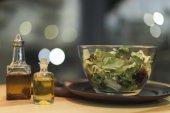Fotografie zblízka pohled čerstvý salát v misce a oleje v lahvích na dřevěný povrch