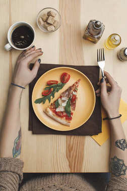 partial view of woman sitting at table with pizza piece on plate and cup of coffee