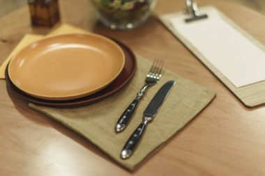 selective focus of cutlery, empty plates and napkins on wooden tabletop