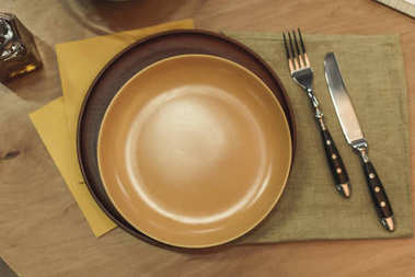 top view of empty plates, cutlery and napkins on wooden surface