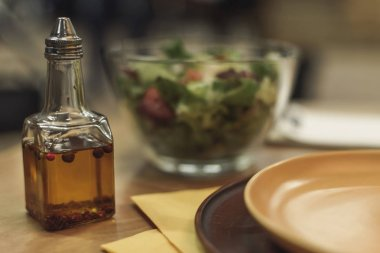 selective focus of oil in bottle, plates and salad in bowl on table