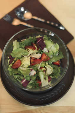 selective focus of fresh vegetables salad in bowl on wooden tabletop