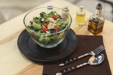 selective focus of fresh vegetables salad in bowl, cutlery on wooden tabletop