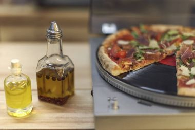 close up view of types of oil in bottles and italian pizza on vinyl record player
