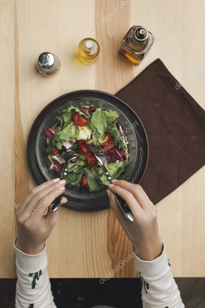 partial view of woman mixing salad in bowl at wooden table