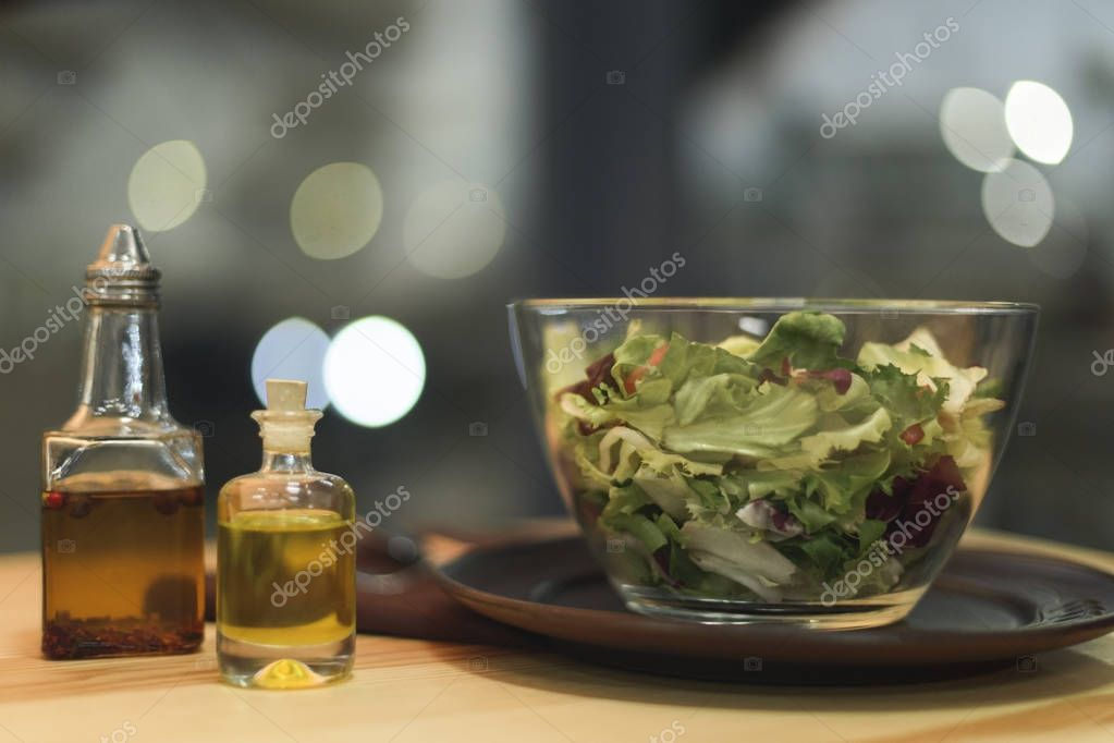 close up view of fresh salad in bowl and oil in bottles on wooden surface