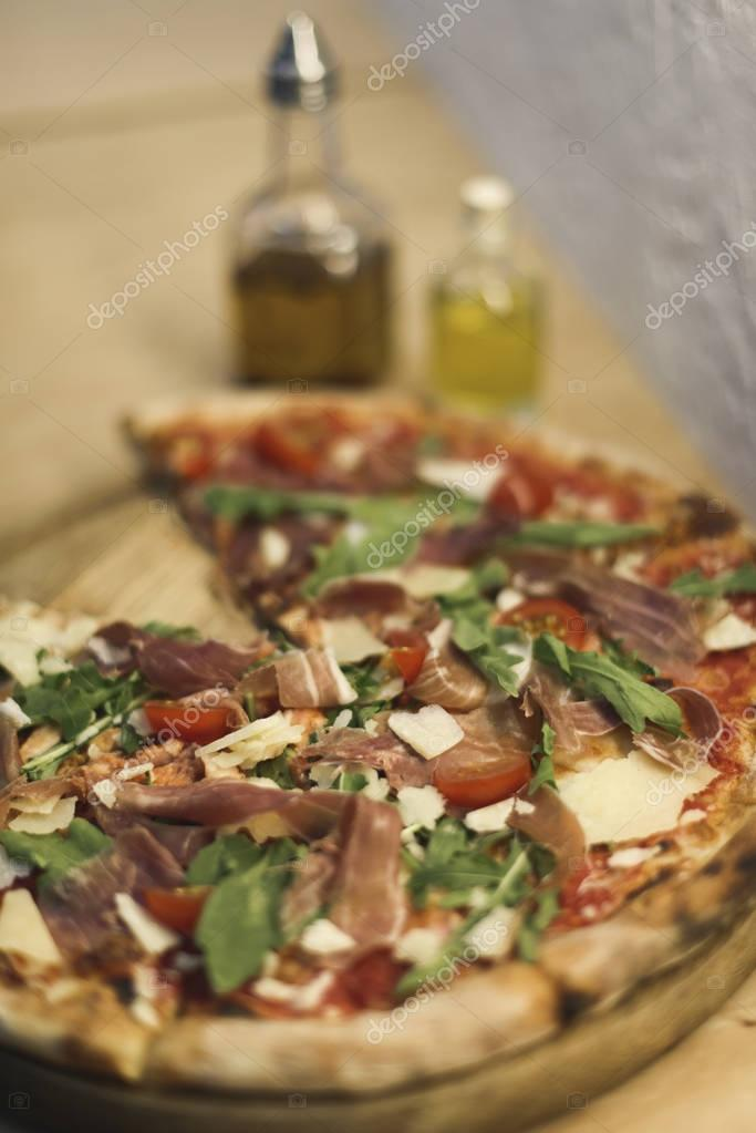 selective focus of tasty homemade italian pizza on wooden board
