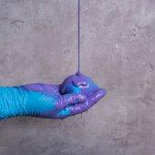 Festék, ömlött a tojás a kezében, szürke háttér