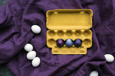 Colored eggs in egg carton and white eggs on textile background