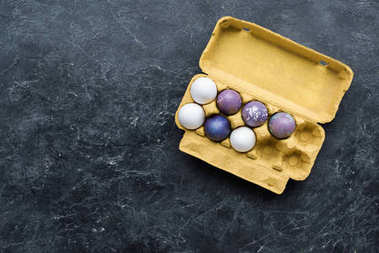 Egg carton with Easter eggs on dark background