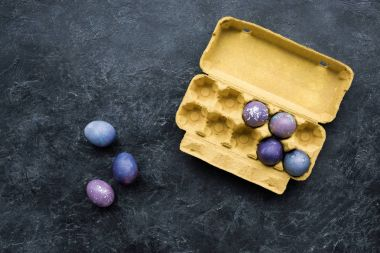 Egg carton with colored eggs on dark background