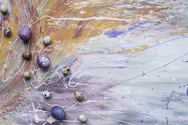 Painted chicken and quail eggs on stained background