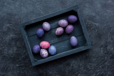 Box with painted chicken and quail eggs on dark background