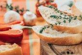 Detailní pohled čerstvá nakrájená bageta na dřevěné krájecí desky a parmezán sýr s paprikou a žampiony na stole
