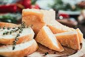 Detailní pohled plátky bagety a lahodný sýr parmezán na dřevěném prkénku