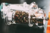 selective focus of salt and peppercorns in glass containers