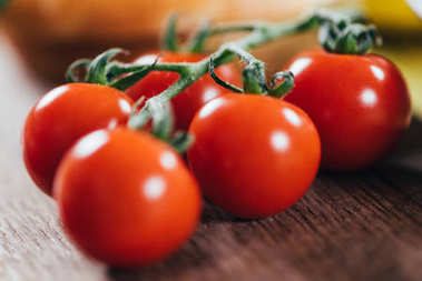 close-up view of fresh ripe organic cherry tomatoes on wooden table