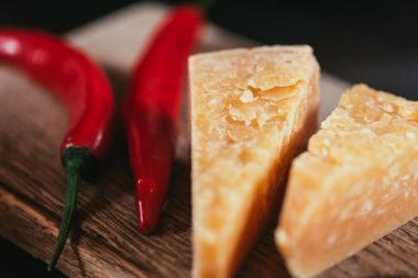 close-up view of gourmet parmesan cheese and chili peppers on wooden cutting board