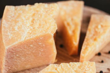 close-up view of gourmet parmesan cheese with peppercorns on wooden cutting board
