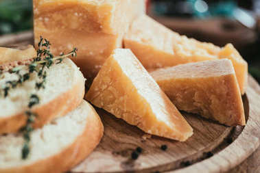 close-up view of delicious parmesan cheese and slices of fresh baguette on wooden cutting board