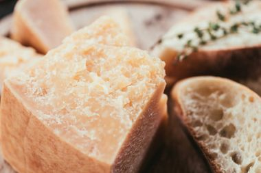close-up view of gourmet parmesan cheese and slices of fresh bread on wooden cutting board