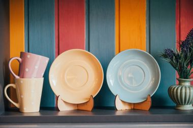 close-up view of decorative empty plates and cups near colorful wall in restaurant
