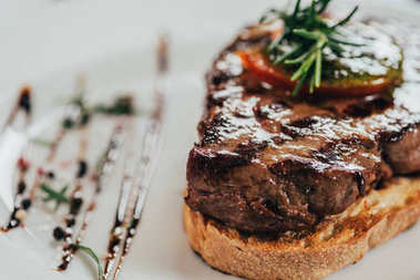 selective focus of delicious juicy beef steak with rosemary and roasted bread on plate