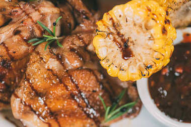 top view of delicious roasted chicken with rosemary and grilled corn