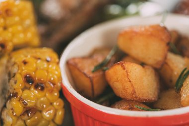 close-up view of tasty grilled corn with roasted potatoes on plate