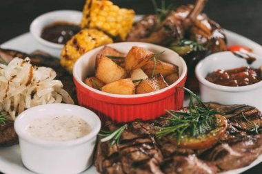 close-up view of grilled vegetables, roasted chicken wings and beef steaks with potatoes on plate