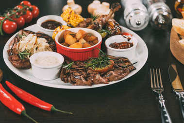 plate with sauces, roasted potatoes, grilled meat and vegetables on table