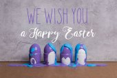 Photo Paint covering eggs in cups with we wish you happy easter lettering on grey background